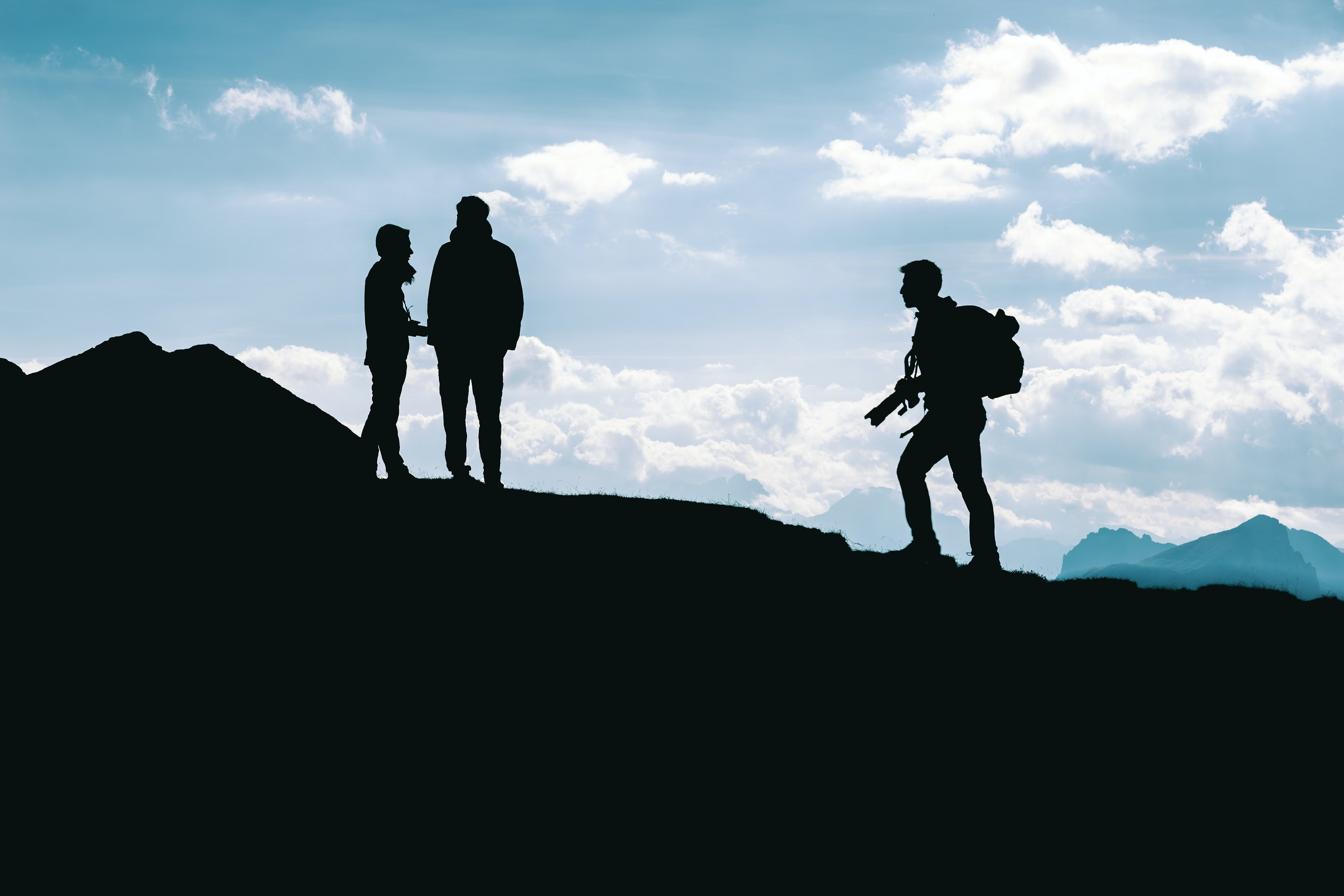 silhouette photo of three person standing on top of cliff