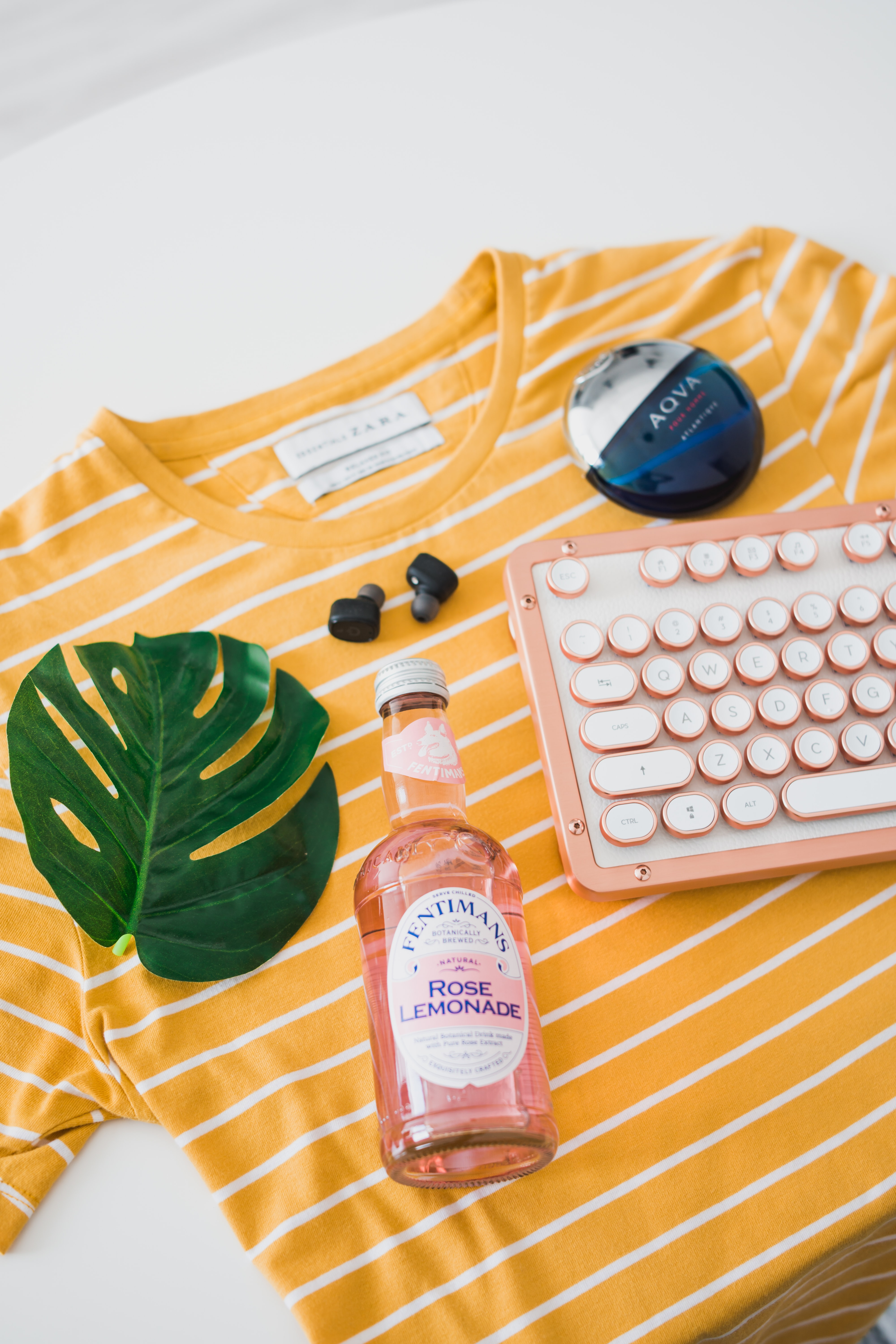 bottle and keyboard on striped crew-neck shirt