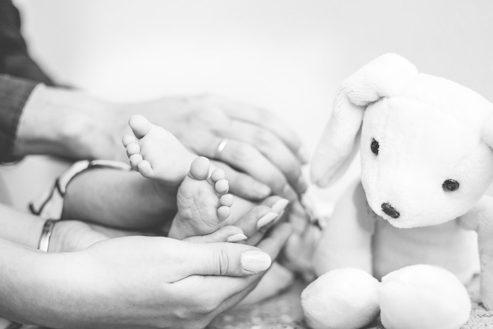 grayscale photography of person's hands holding baby's feet