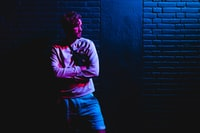 man standing beside brick wall