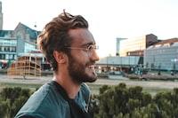 smiling man wearing eyeglasses near trees and buildings