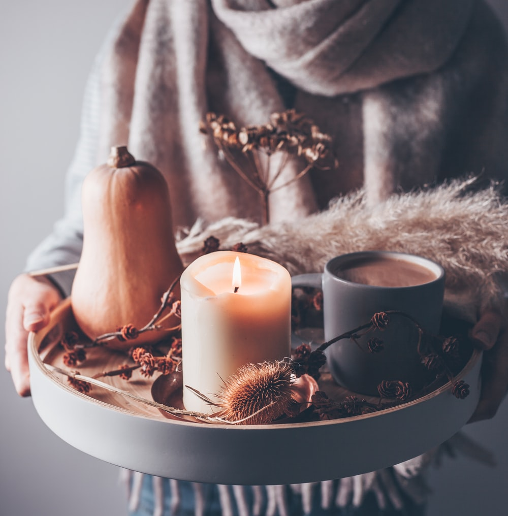 person holding beige pillar candle on gray wooden tray