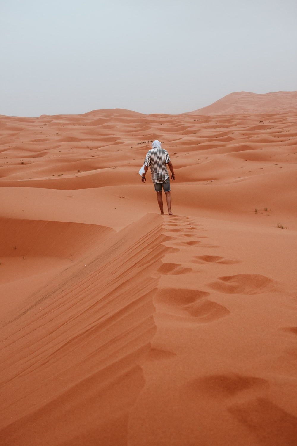 man wearing gray shirt walking on desert