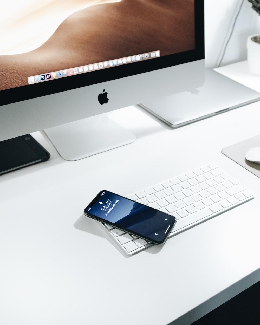 black smartphone on white Apple Magic keyboard