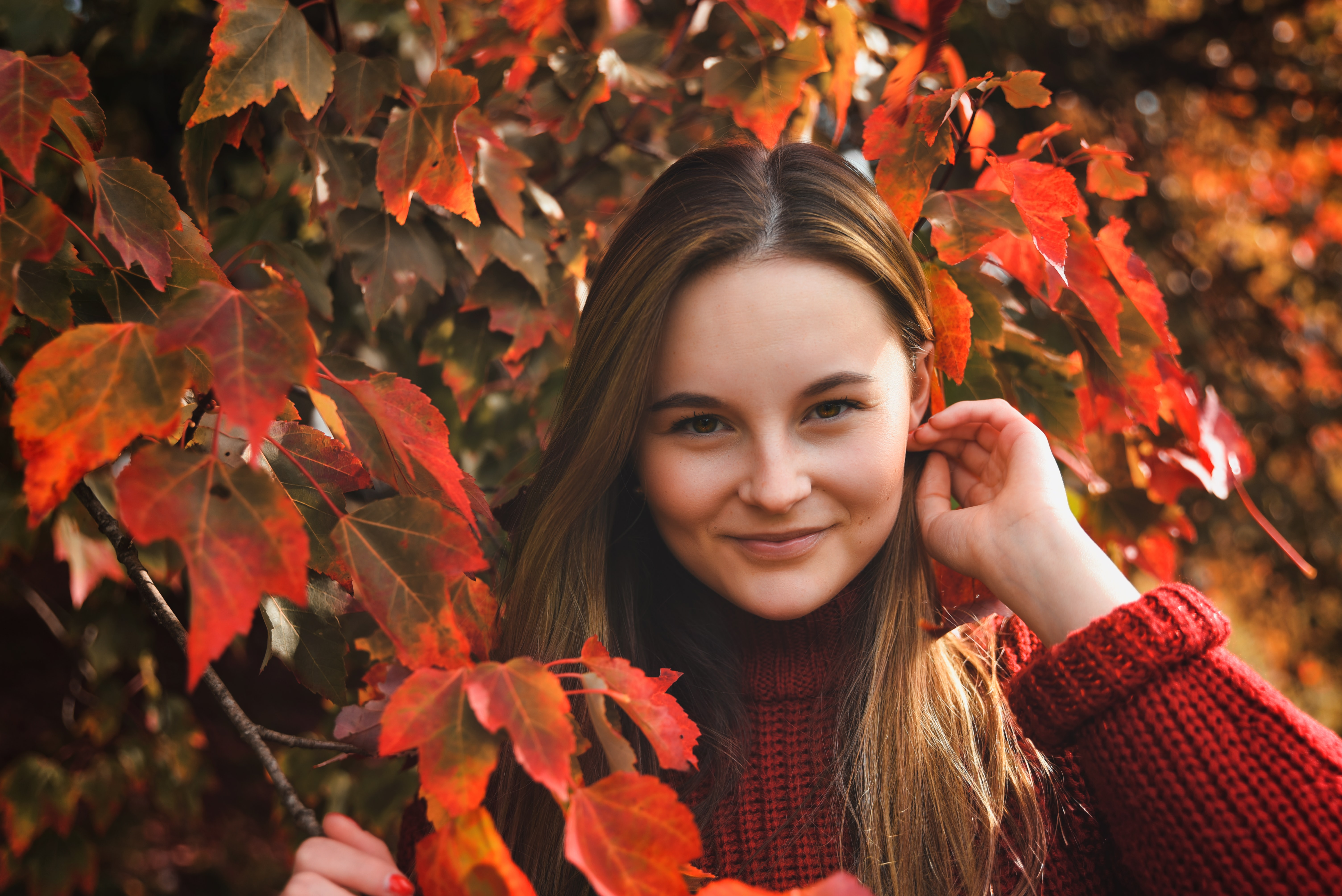 woman standing beside red leaves