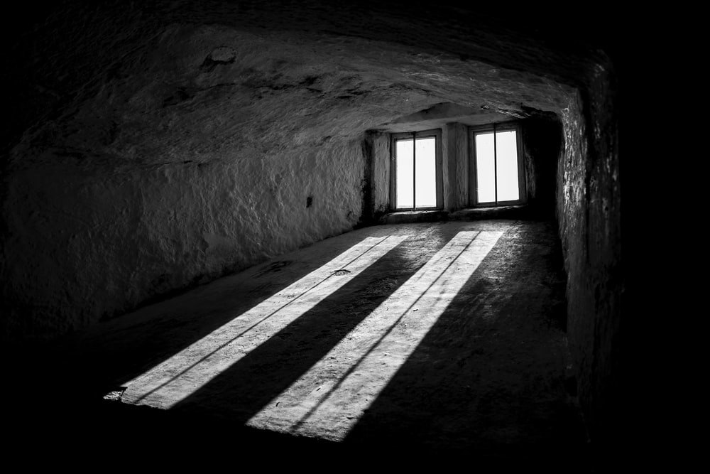 grayscale photography of tunnel with windows