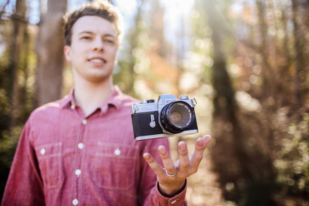 man holding black and gray camera at daytime