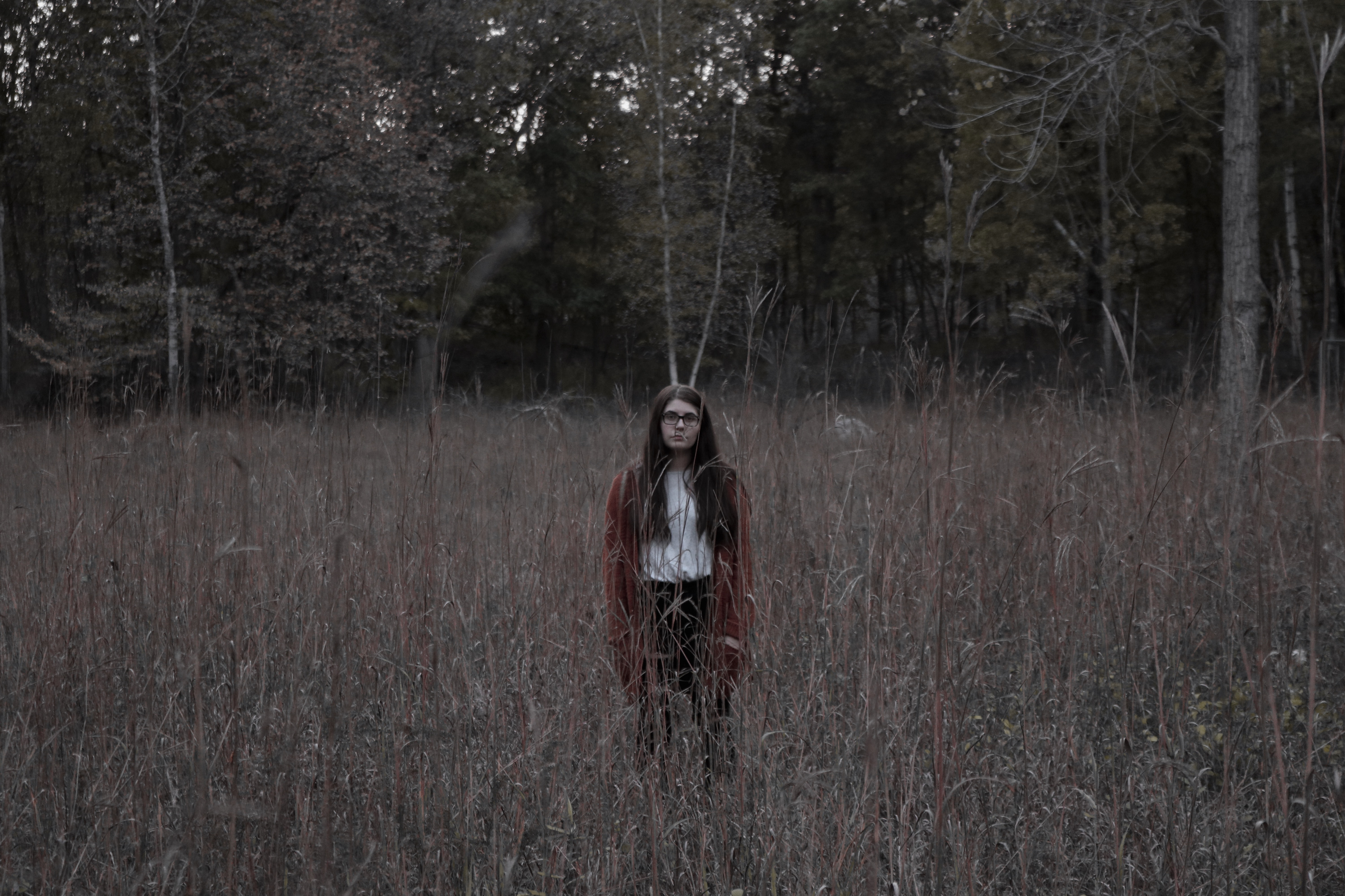 woman standing on the ground surrounded by grass