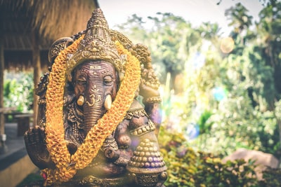 selective focus photography of lord ganesha hindu deity golden statue bali teams background