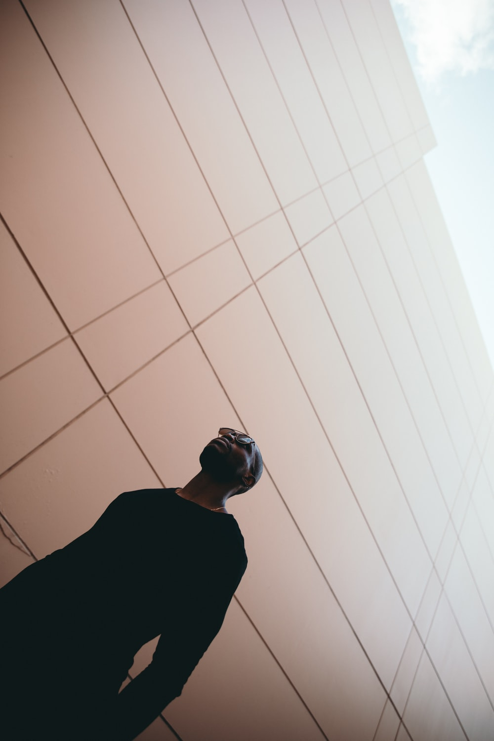 worm's-eye view photography of man standing near beige building