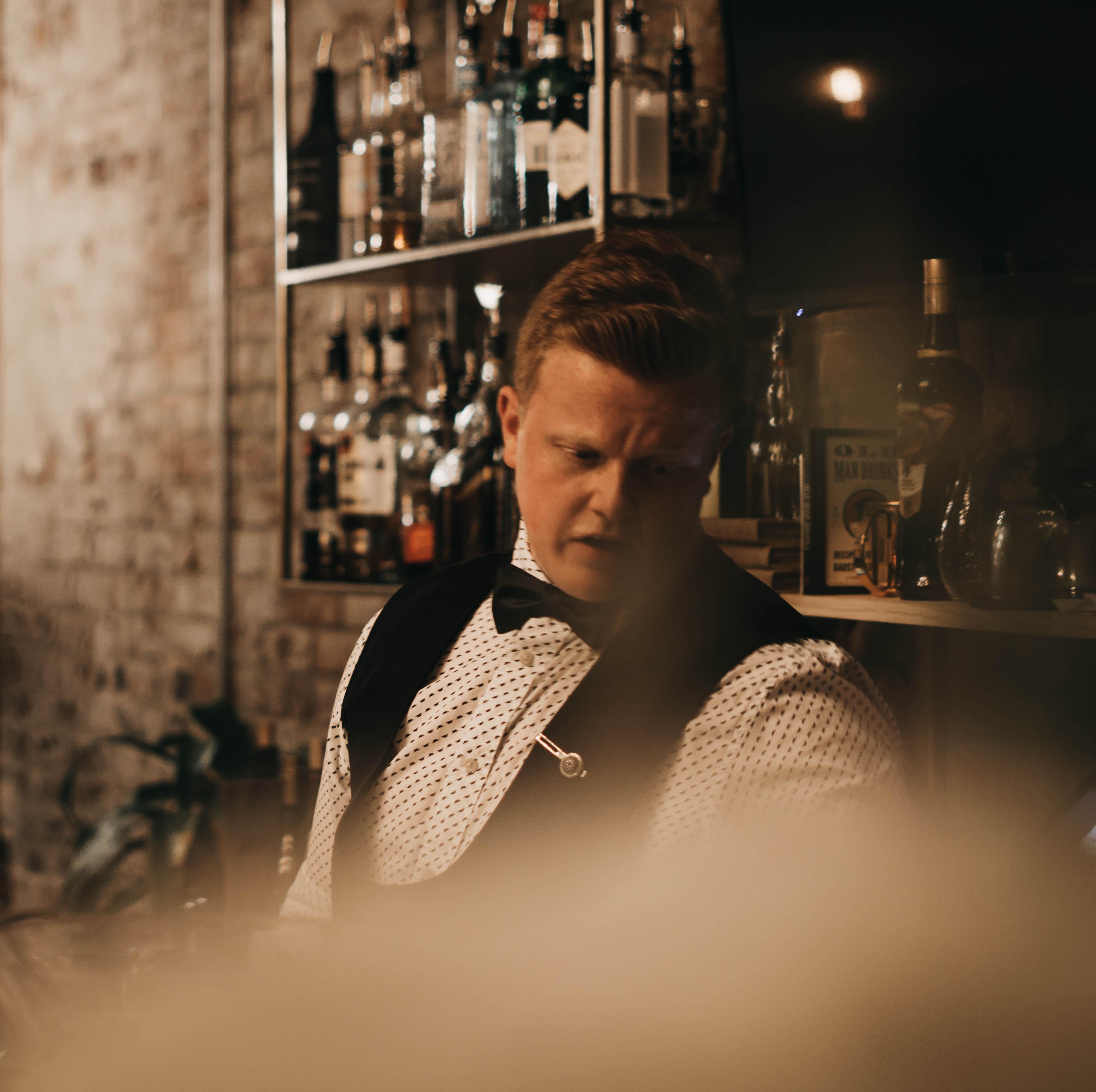 bartender standing in front of floating shelf with bottles