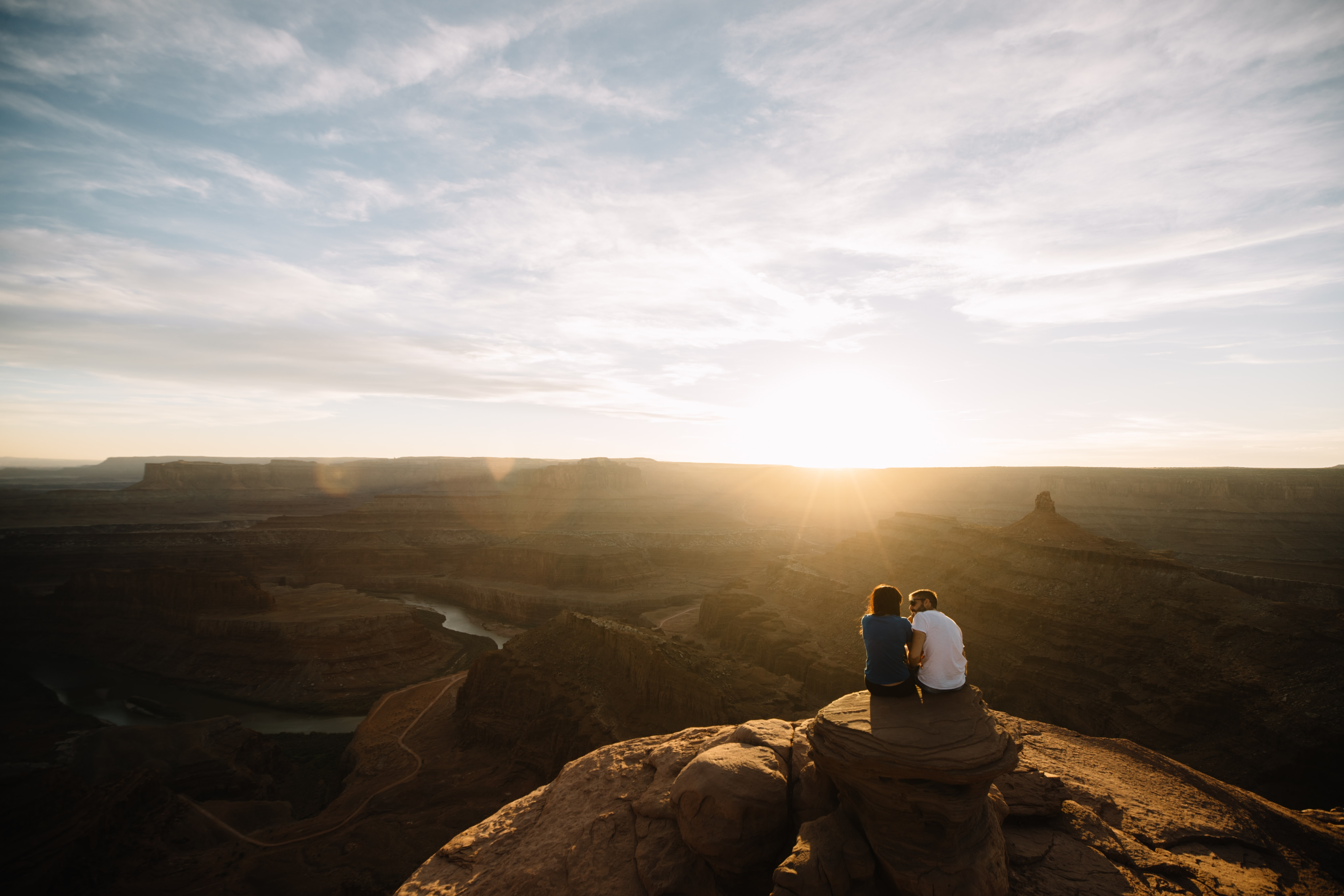 two people sitting on mountain cliff under cloudy sky during golden hour