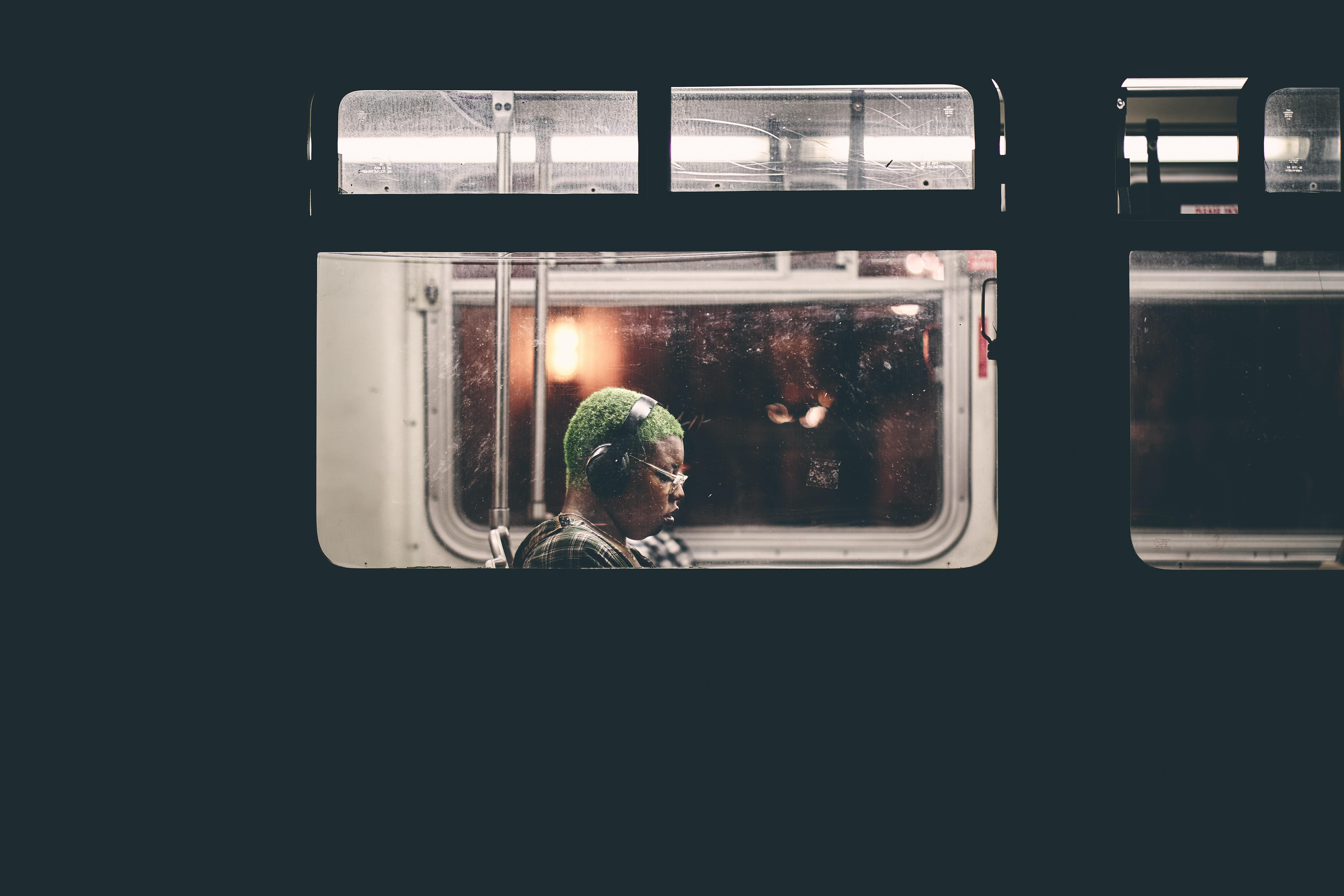 man sitting inside train wearing black headphones