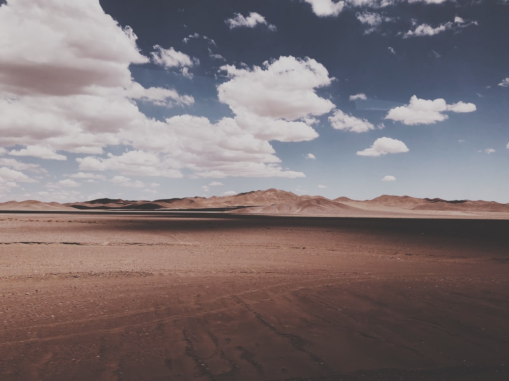 landscape photography of desert under cloudy sky during daytime