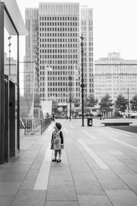 grayscale photo of girl standing near high-rise buildings