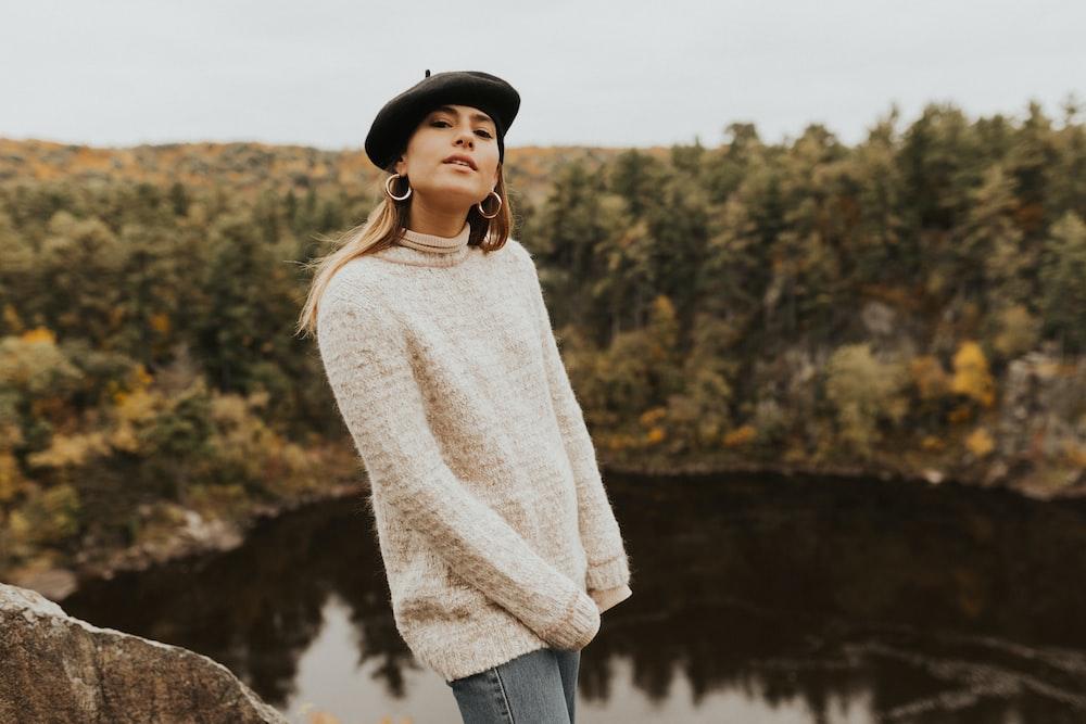 woman wearing beige sweater on top of hill