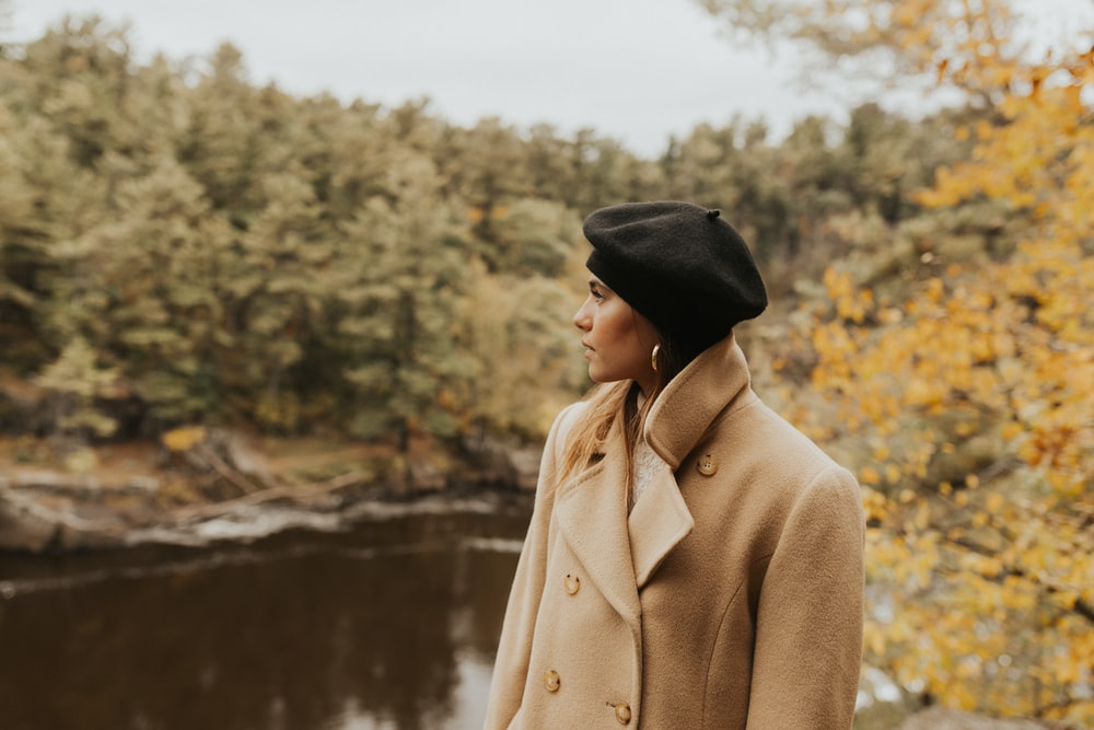 woman standing looking her right side near lake