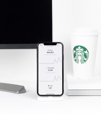 iPhone X beside Starbucks disposable cup on desk