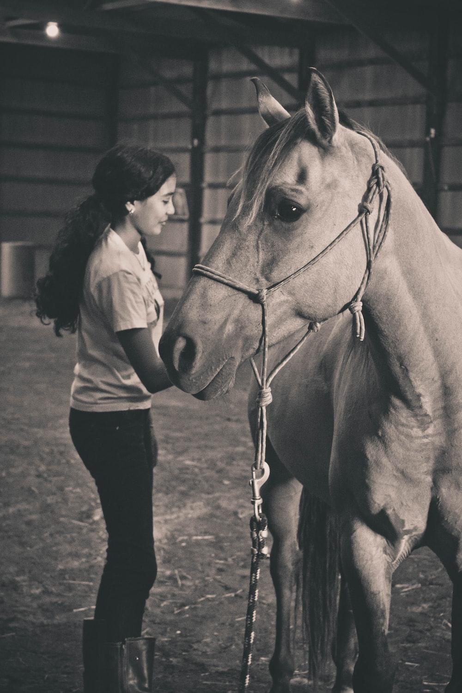 woman standing near horse