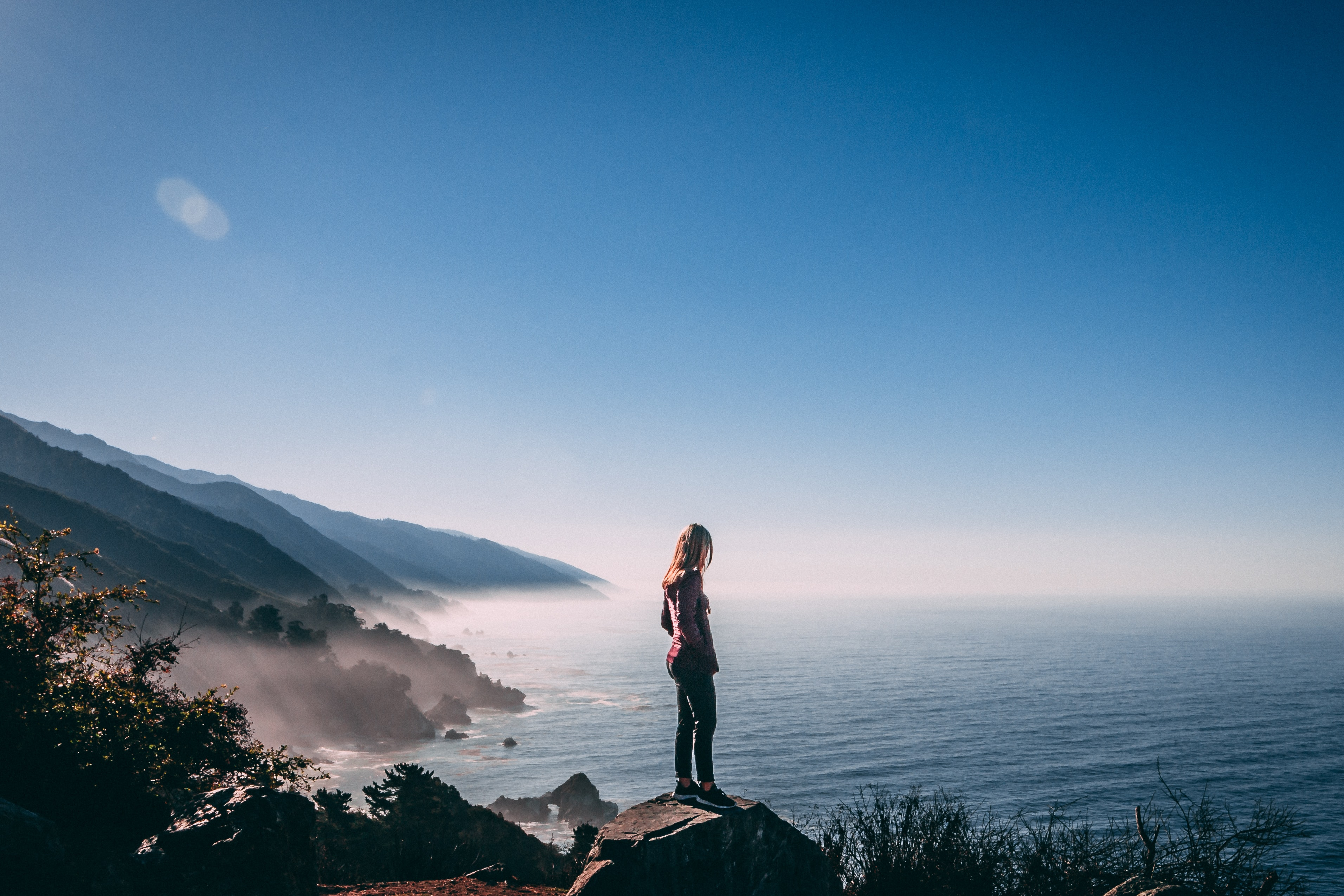 woman standing on cliff near sea