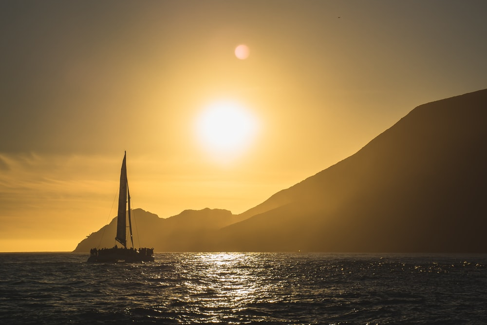 landscape photo of a sunset on a sea with sailboat