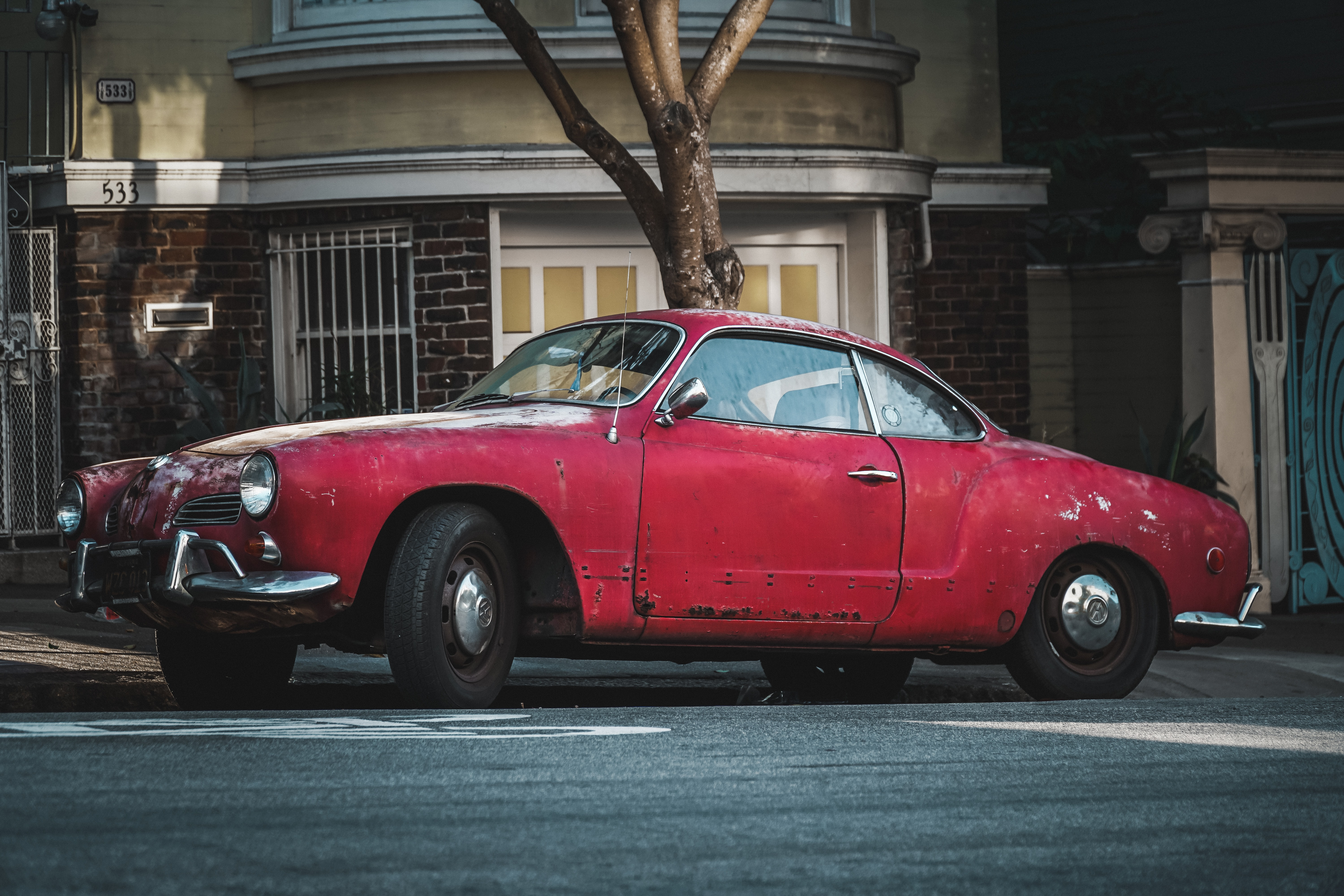 classic red coupe parked beside concrete curb