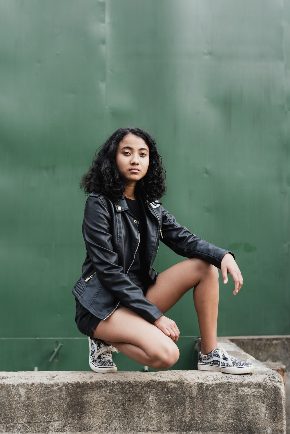 woman wearing black zip-up jacket and short shorts in sitting position during daytime