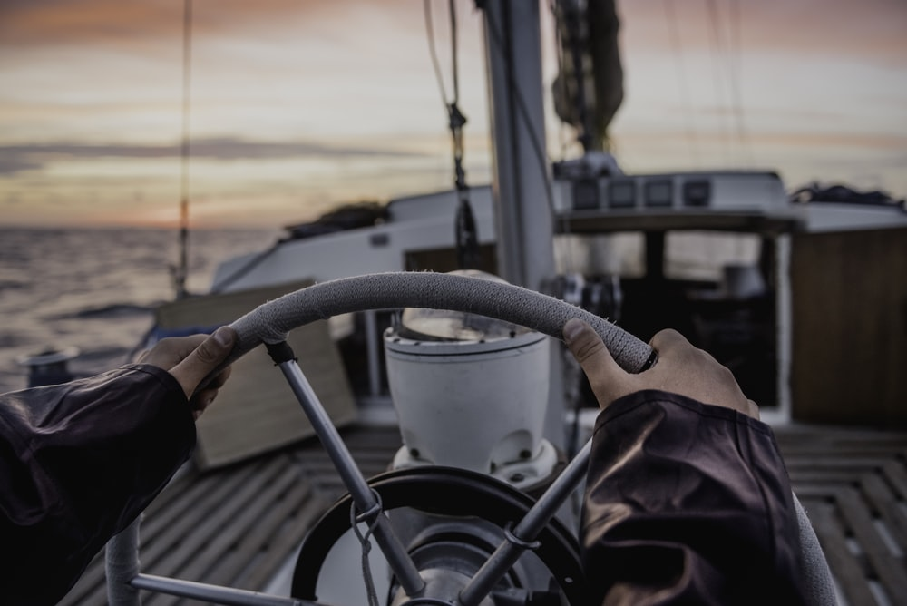 selective focus photography of person grabbing on boat steering wheel