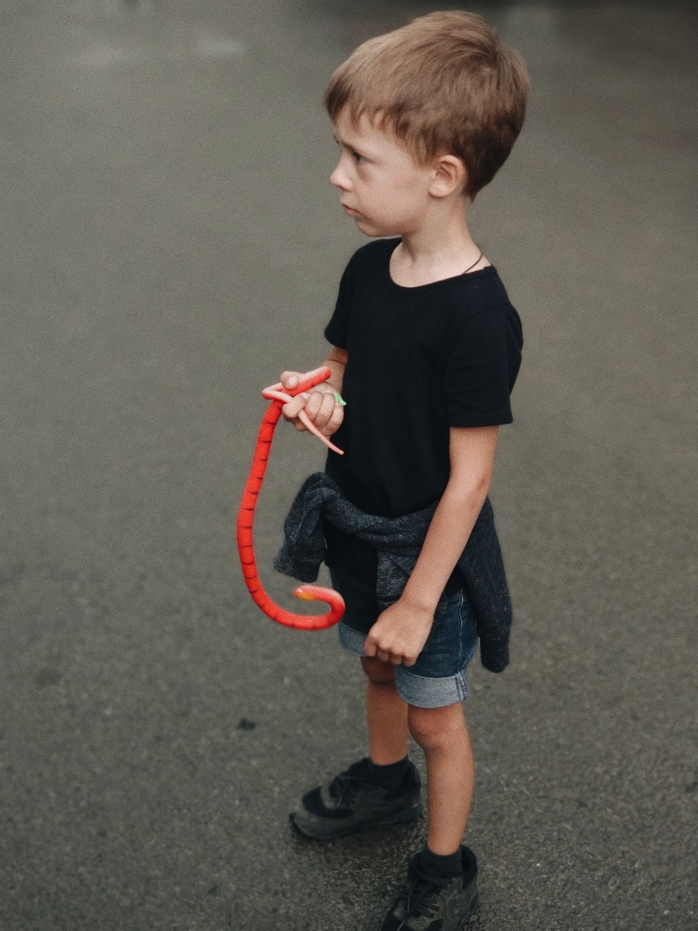 boy holding red snake toy