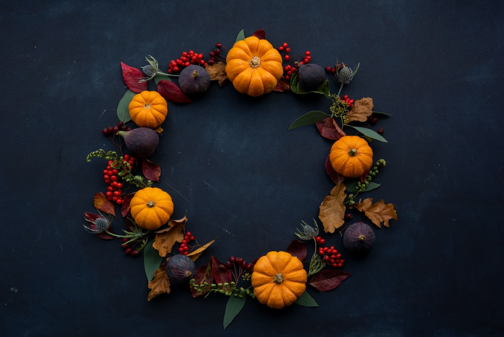 round Halloween-themed wreath on blue surface