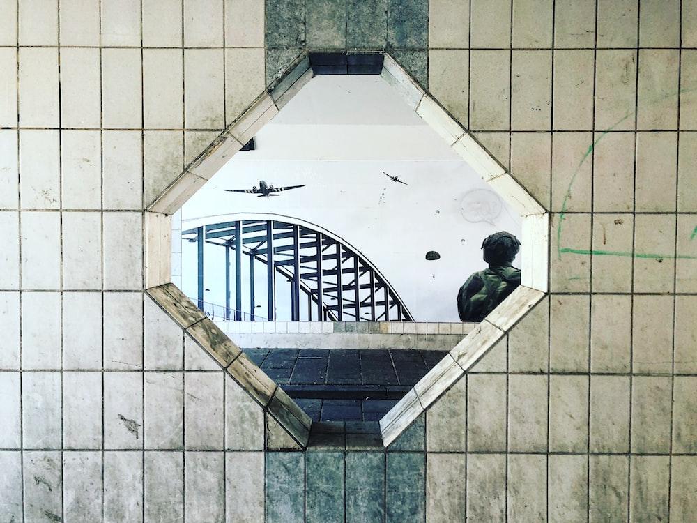 mirror displaying planes and concrete bridge
