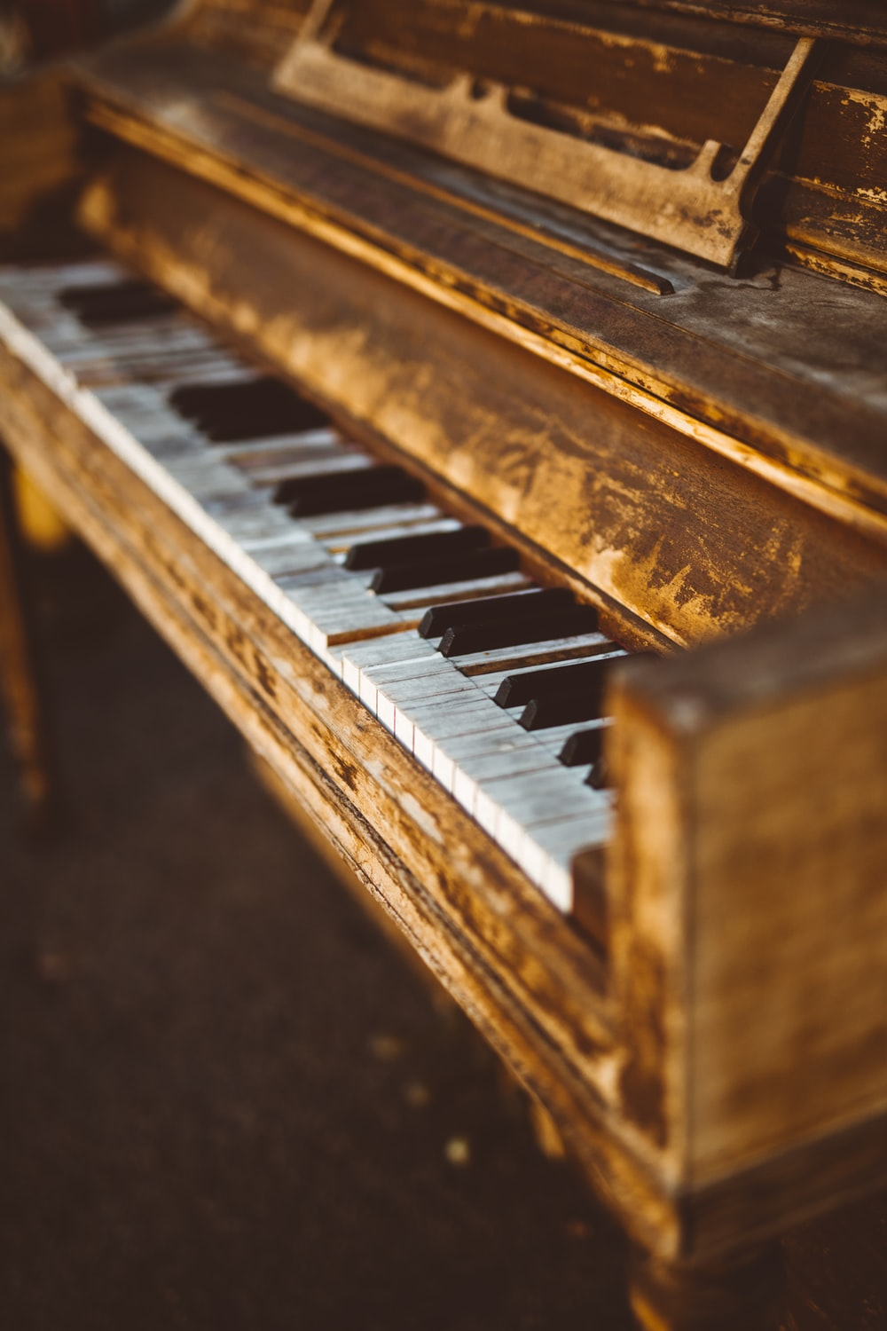 selective focus photogrpahy of brown wooden console piano