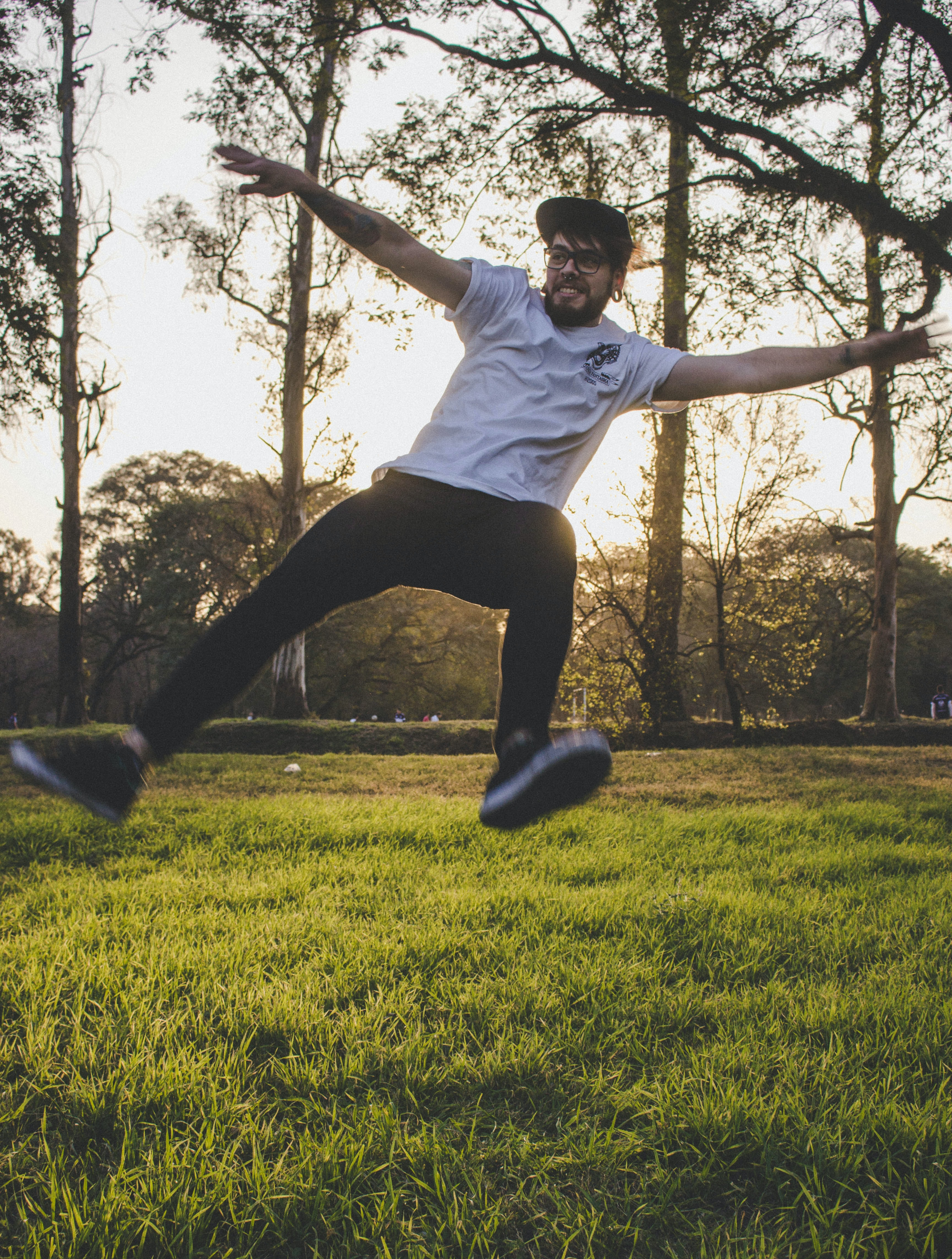 man jumping above green grass with trees behind during golden hour