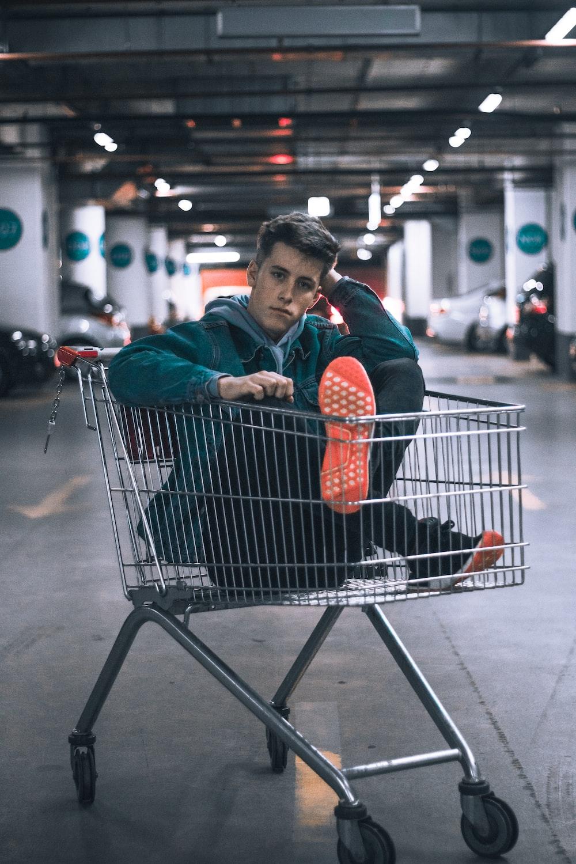 man in shopping cart inside building parking lot
