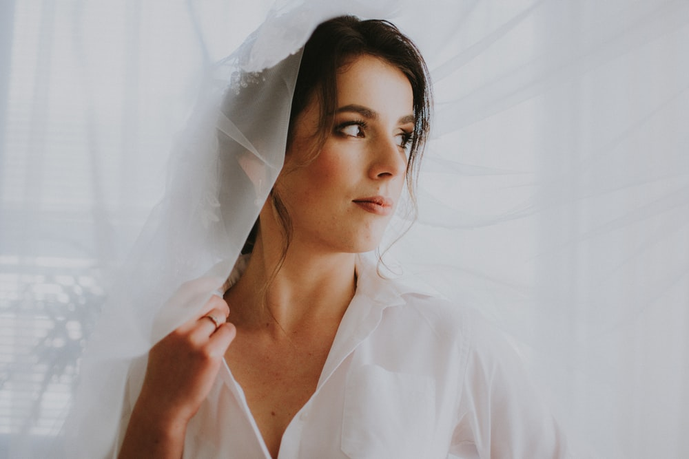 woman wearing white collared top with veil