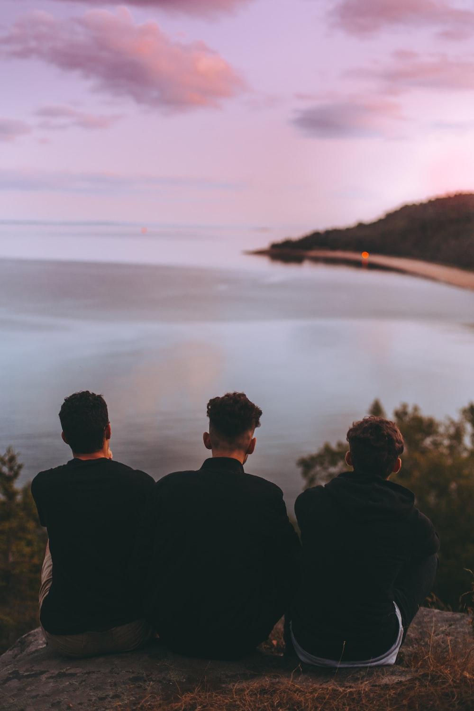 three men sitting near body of water
