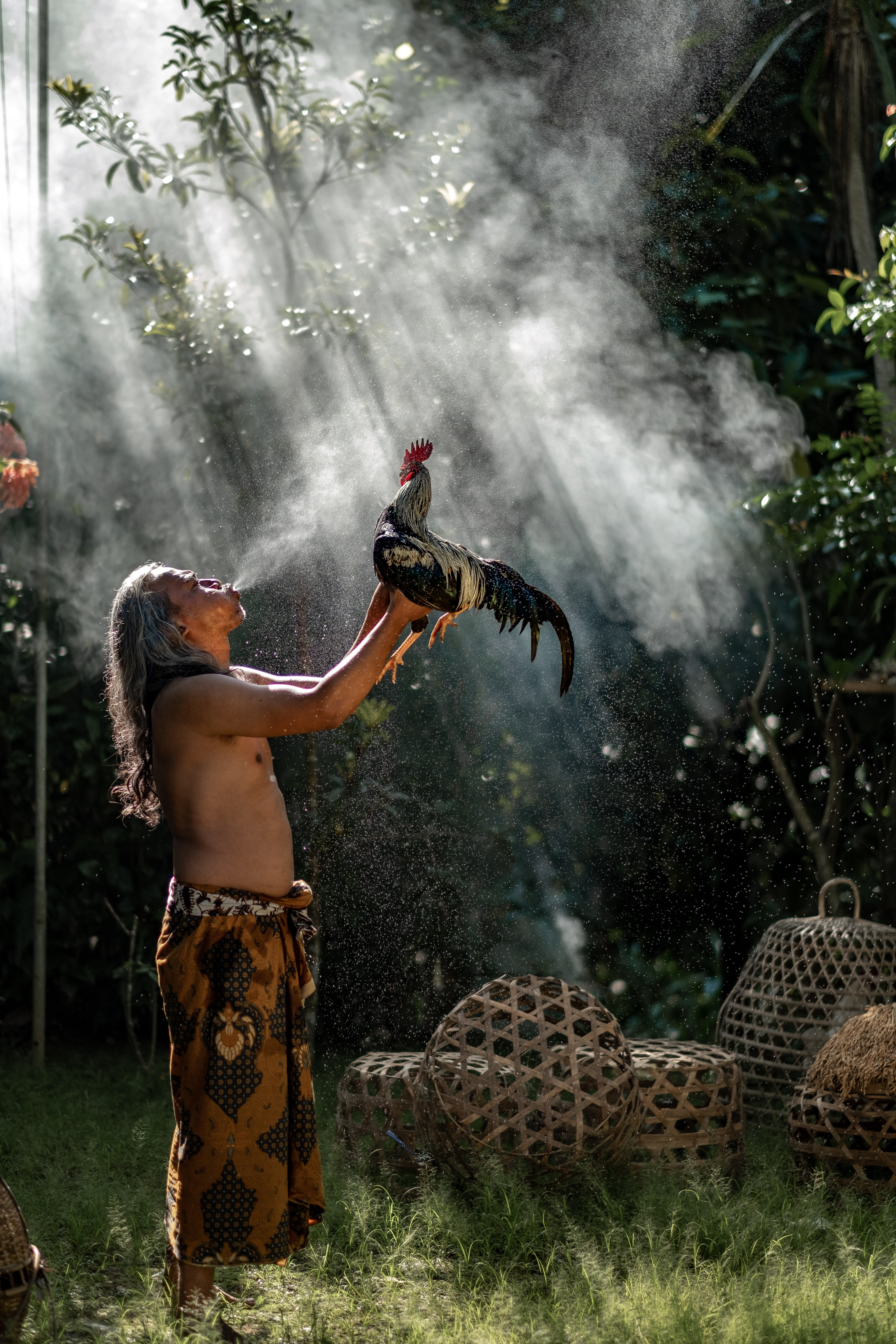 man raising rooster while blowing smoke during daytime
