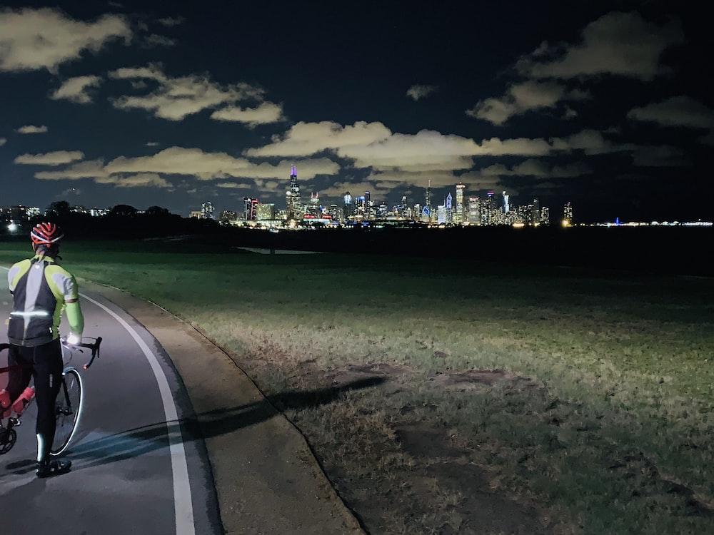 biker riding bike near lighted city buildings