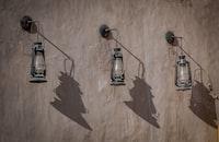 three oil lanterns hanging on brown wall