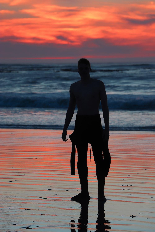 silhouette of man near ocean