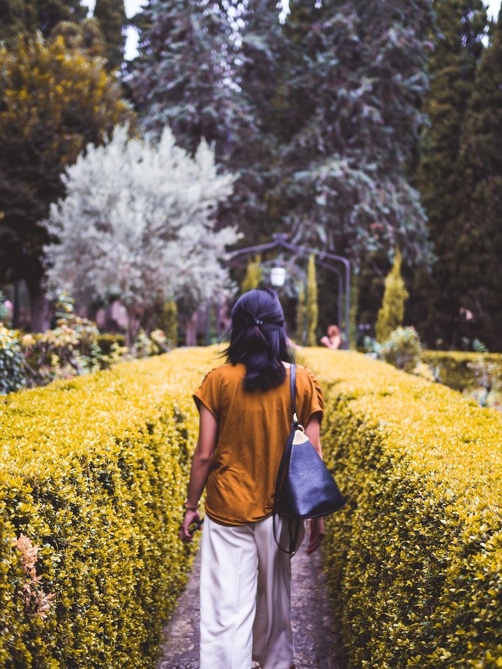 woman walking between green bushes during daytime