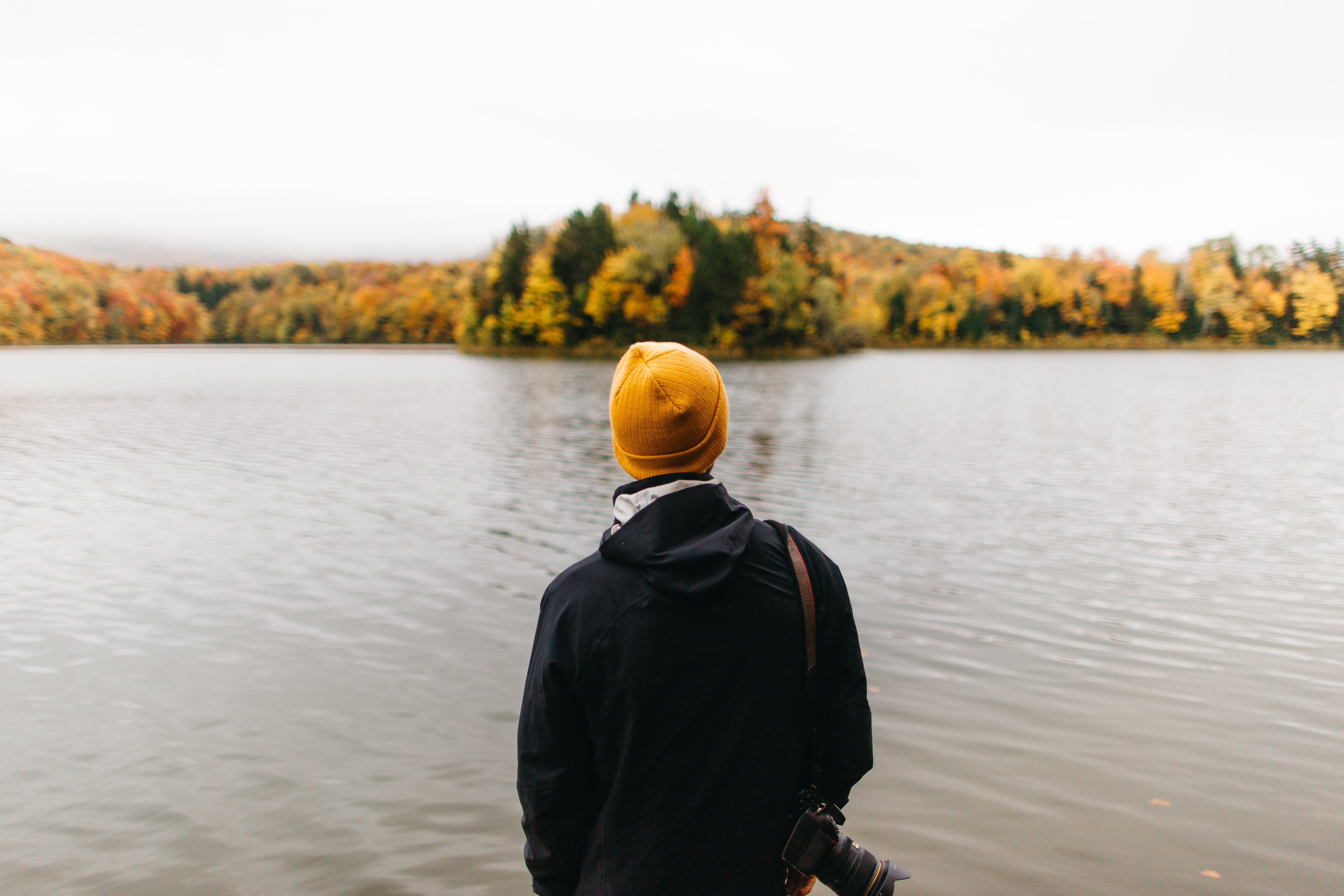 person standing facing body of water