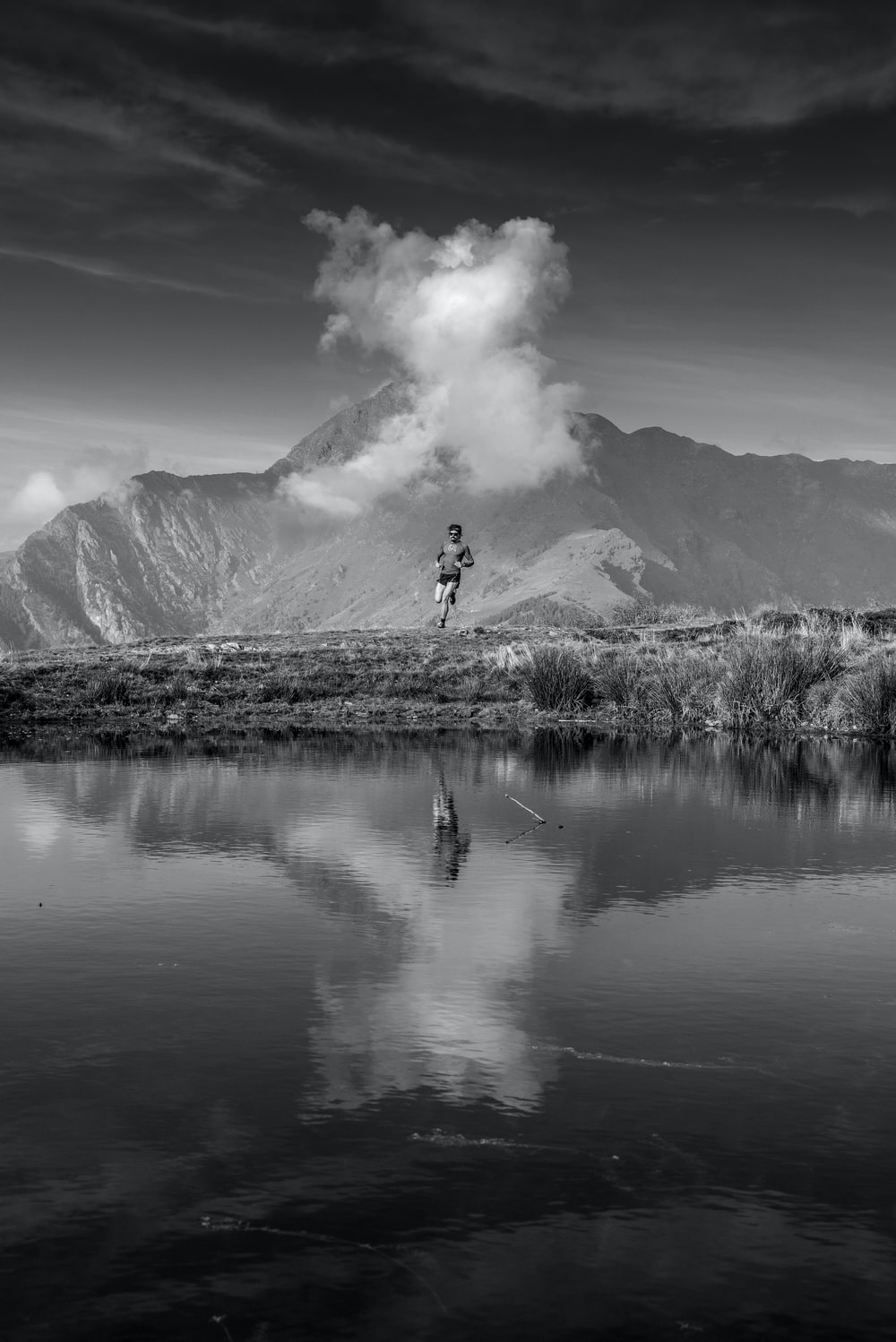grayscale photo of man jump over calm body of water
