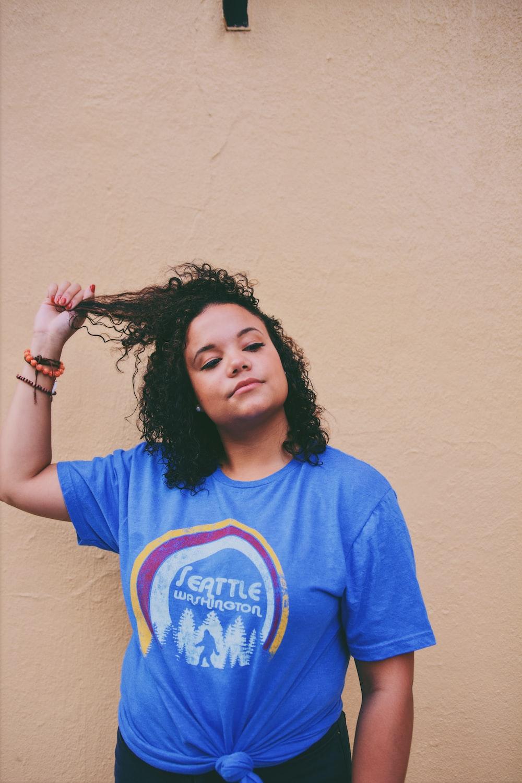 woman wearing blue shirt standing near white wall