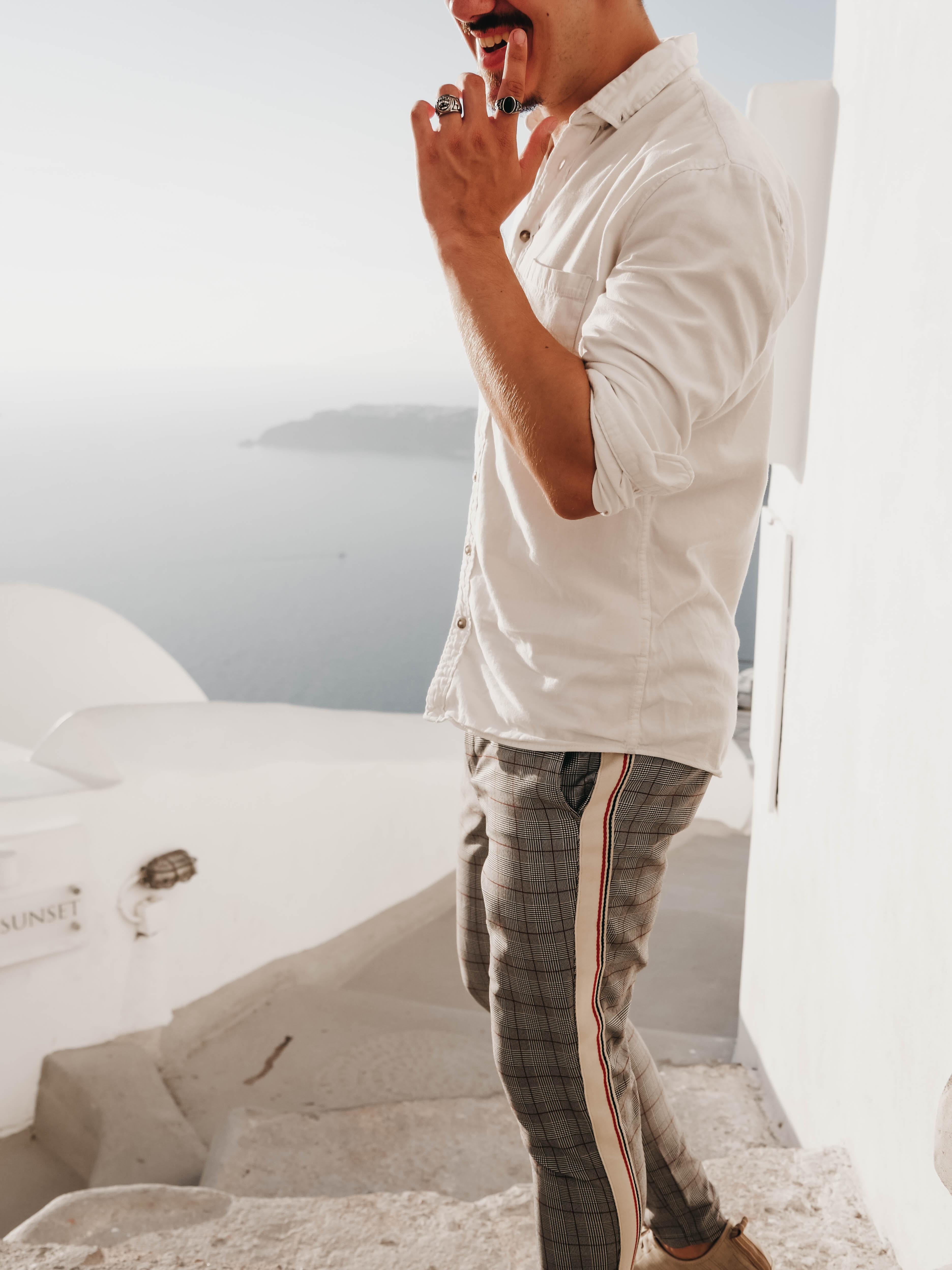 man wearing white dress shirt and gray pants