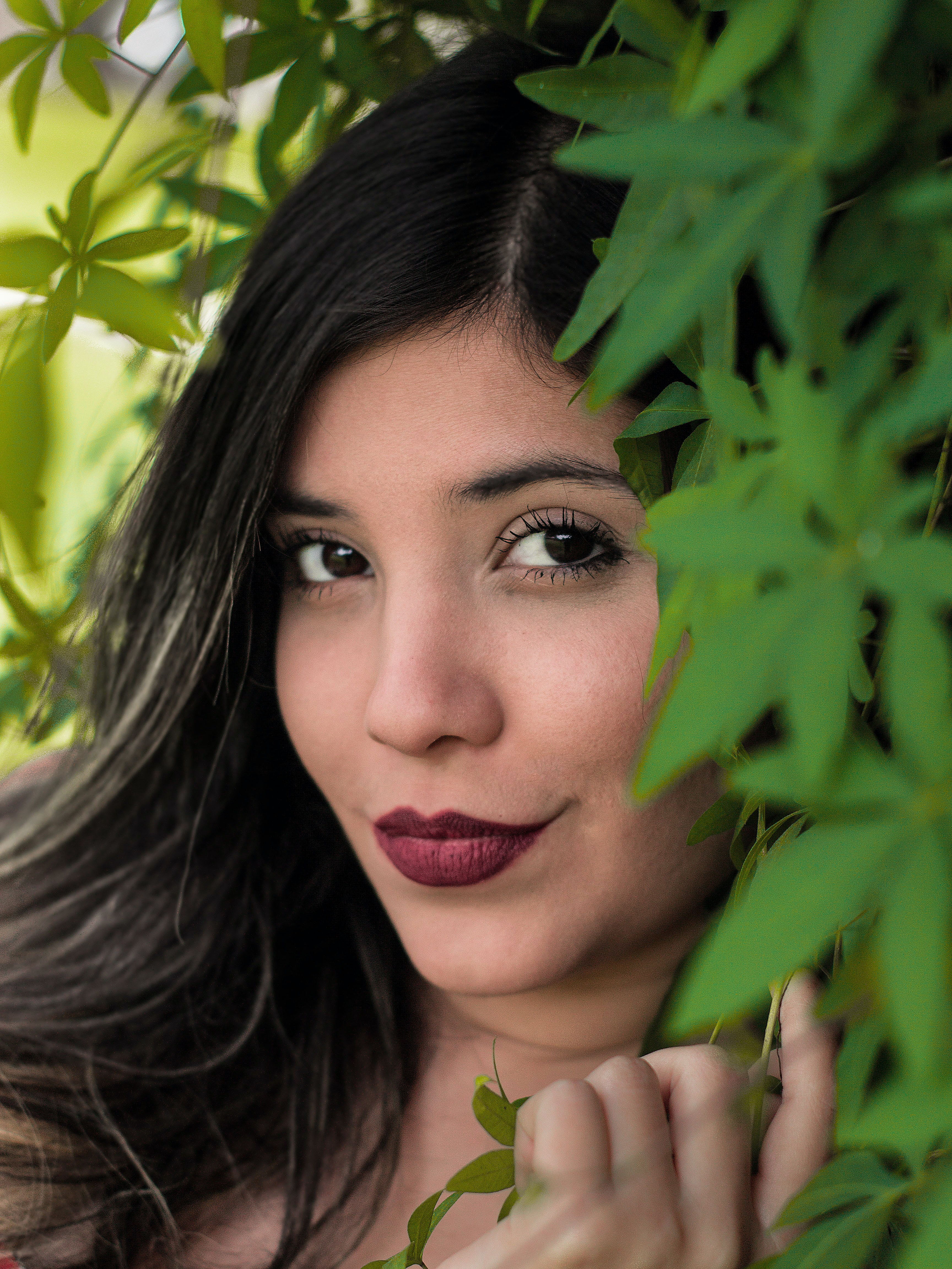 woman taking selfie next to green leaf plant