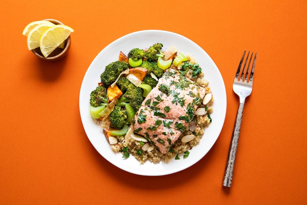 Platillo con salmón, granos y vegetales.