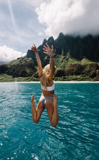 woman jumping on cliff into water while raising hands and folding both knees
