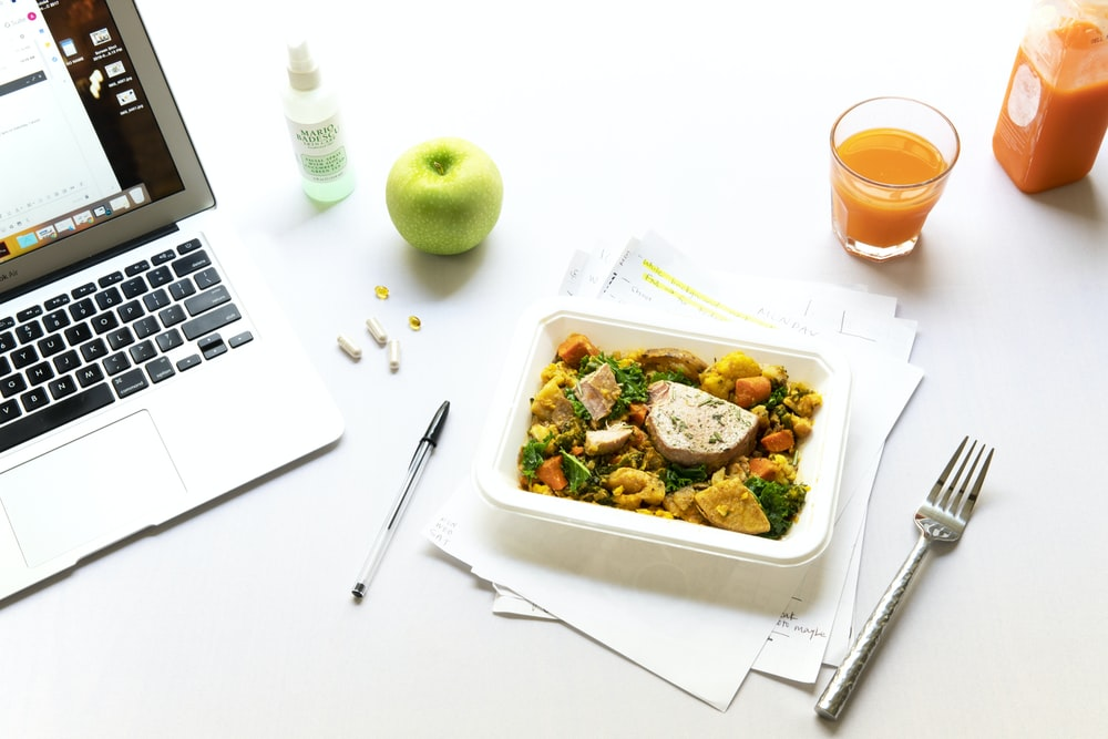 vegetables on plate beside fork and laptop