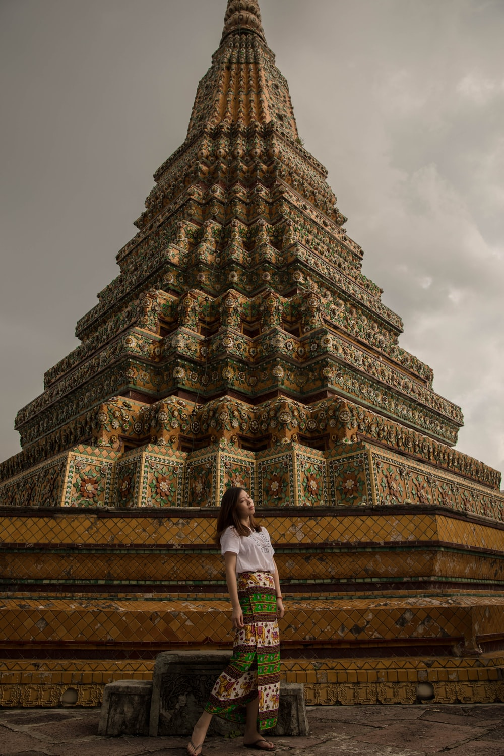 woman standing beside pagoda temple